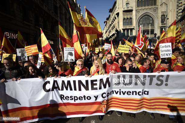 Demonstrators wave Spanish and Catalan flags marching behind a banner reading 'Let's walk together Respect and coexistence' during an...