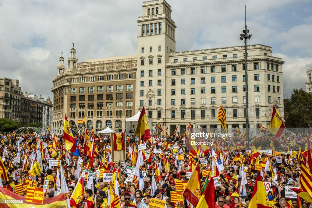 Demonstrators wave Spanish national flags and placards reading 'De Todos' or 'All' as they gather on Catalonia Square in support of Spanish unity during a march on Spain's National Day in Barcelona, Spain, on Thursday, Oct. 12, 2017. Prime Minister Mariano Rajoy gave his Catalan antagonist Carles Puigdemont five days to clarify whether he has declared independence from Spain or not as the country prepared for its national holiday on Thursday. Photographer: Angel Garcia/Bloomberg via Getty Images