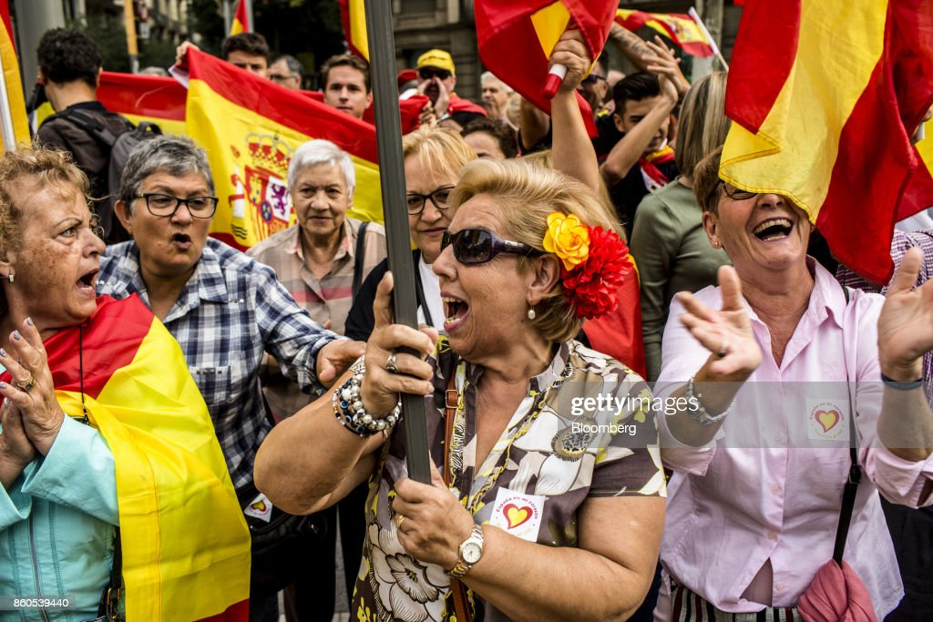 Demonstrators wave Spanish national flags in support of Spanish unity during a march on Spain's National Day in Barcelona, Spain, on Thursday, Oct. 12, 2017. Prime Minister Mariano Rajoy gave his Catalan antagonist Carles Puigdemont five days to clarify whether he has declared independence from Spain or not as the country prepared for its national holiday on Thursday. Photographer: Angel Garcia/Bloomberg via Getty Images