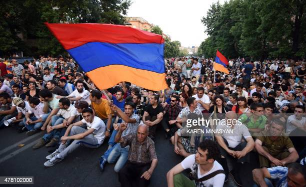Demonstrators wave their national flags as they sit during a protest against the increase of electricity prices in Yerevan the capital of Armenia on...
