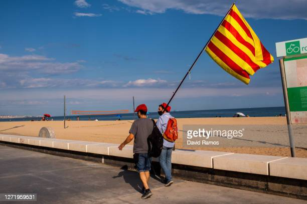 Demonstrators waves a Catalan flag as they walk along the corniche before a Catalan Pro-Independence demonstration on September 11, 2020 in Badalona...