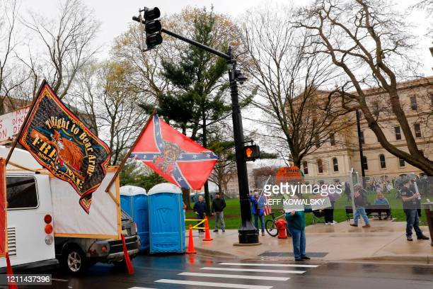 Demonstrators waving a Confederate States flag take part in an American Patriot Rally organized on April 30 by Michigan United for Liberty on the...