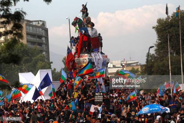 Demonstrators waving Chilean and Wenufoye flags climb the Plaza Italia monument during a protest against president Sebastian Piñera to commemorate...