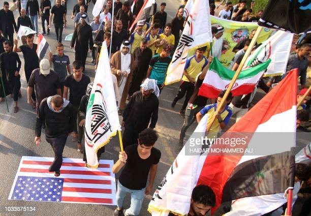 Demonstrators waving Iranian and proIranian party flags step on a US flag during a protest on September 15 against the torching of the Iranian...