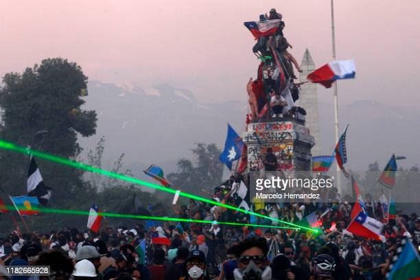 Demonstrators waving Wenufoye and Chilean flags climb the Plaza Italia monument as a green laser points at riot police during protests against...