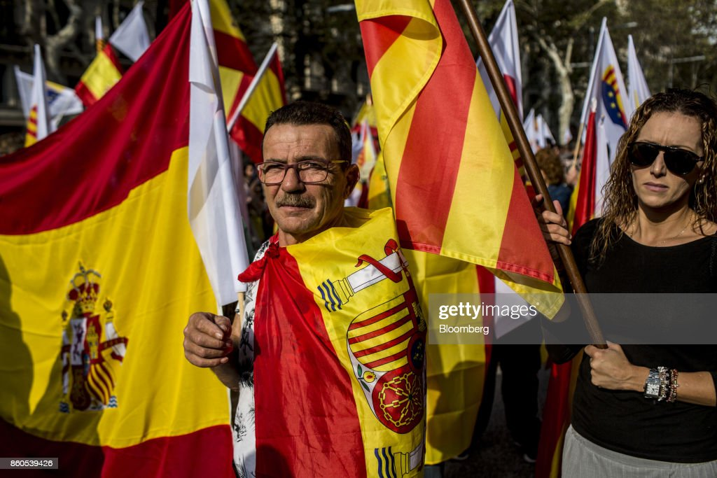 Demonstrators wear and hold Spanish national flags in support of Spanish unity during a march on Spain's National Day in Barcelona, Spain, on Thursday, Oct. 12, 2017. Prime Minister Mariano Rajoy gave his Catalan antagonist Carles Puigdemont five days to clarify whether he has declared independence from Spain or not as the country prepared for its national holiday on Thursday. Photographer: Angel Garcia/Bloomberg via Getty Images