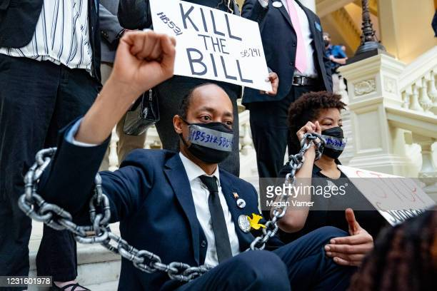 Demonstrators wear chains while holding a sit-in inside of the Capitol building in opposition of House Bill 531 on March 8, 2021 in Atlanta, Georgia....