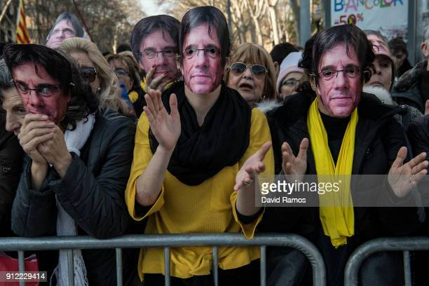 Demonstrators wear cutout masks of the former Catalan President Carles Puigdemont as they take part in a protest on January 30 2018 in Barcelona...