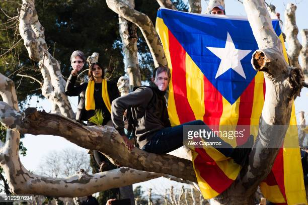 Demonstrators wear cut-out masks of the former Catalan President Carles Puigdemont as they take part in a protest in front of the Parliament of...