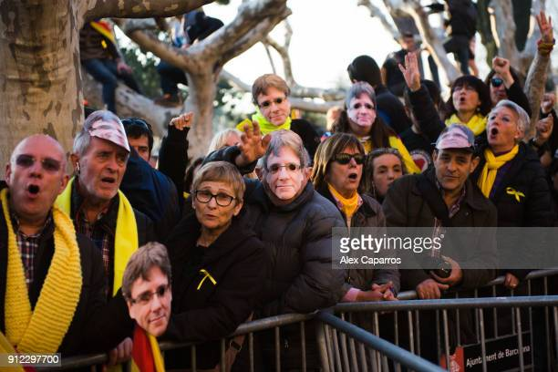 Demonstrators wear cutout masks of the former Catalan President Carles Puigdemont as they take part in a protest in front of the Parliament of...