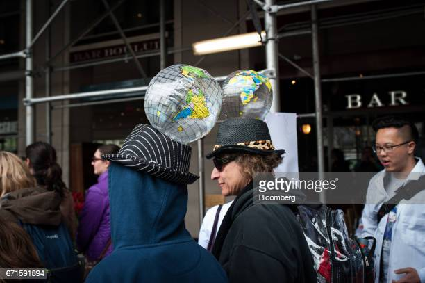 Demonstrators wear inflatable globes on hats as they attend the March for Science rally on Earth Day in New York US on Saturday April 22 2017 The...