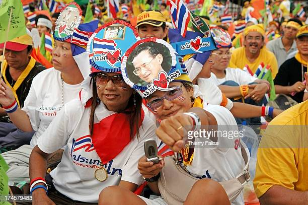 Demonstrators wear makeshift hats with pictures of the revered Thai King as an estimated crowd of 100000 people gathered in Bangkok to support the...
