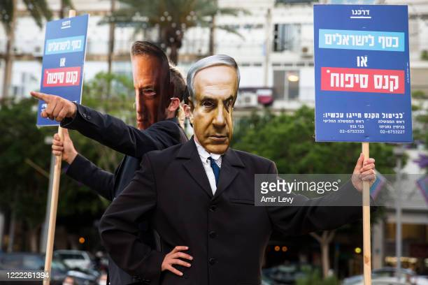 Demonstrators wear masks of Israeli Prime Minister Benjamin Netanyahu, and Defense Minister Benny Gantz as they protest against the Israeli...