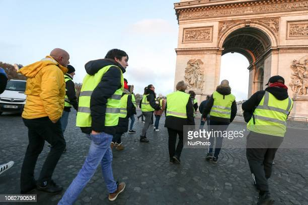 Demonstrators wearing a Yellow Vest block the place CharlesdeGaulle in front of the Arc de Triomphe during a protest against the rising of the fuel...