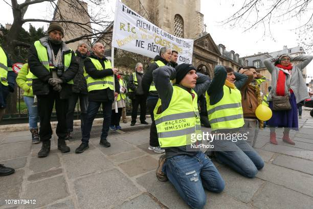 Demonstrators wearing a yellow vest kneel down in Paris on January 5 2019 during a demonstration called by the yellow vests movement for the eighth...