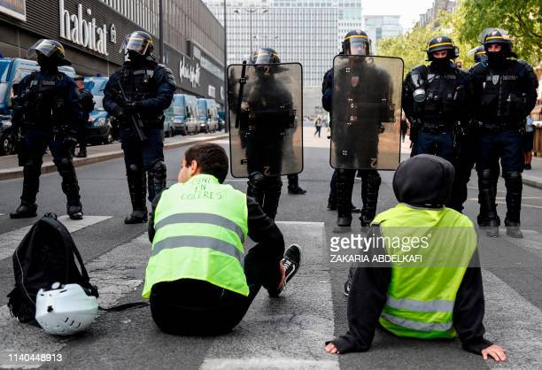 Demonstrators wearing a yellow vest sit in front of riot police officers in the district of Montparnasse prior to the start of May Day demonstrations...