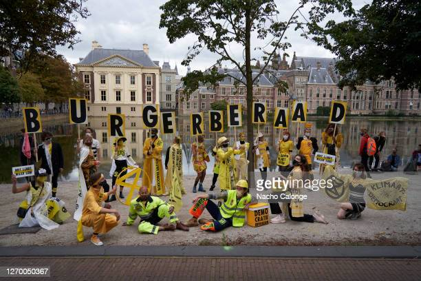 Demonstrators wearing costumes hold placards to ask the government to take into account the opinion of citizens during the demonstration in The Hague...