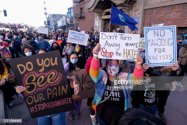 "Demonstrators wearing face masks and holding signs take part in a rally ""Love Our Communities: Build Collective Power"" to raise awareness of..."
