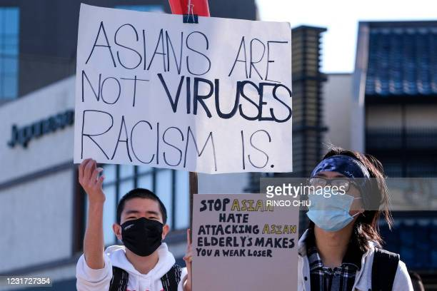 """Demonstrators wearing face masks and holding signs take part in a rally """"Love Our Communities: Build Collective Power"""" to raise awareness of..."""