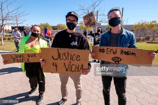 Demonstrators wearing face masks and holding signs take part in a rally to raise awareness of anti-Asian violence, near Chinatown in Los Angeles,...