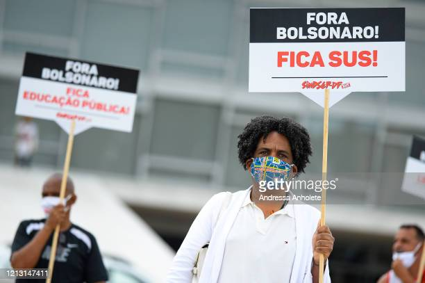 Demonstrators wearing face masks and keeping safe distance hold signs against the President of Brazil Jair Bolsonaro and in favor of life, democracy...