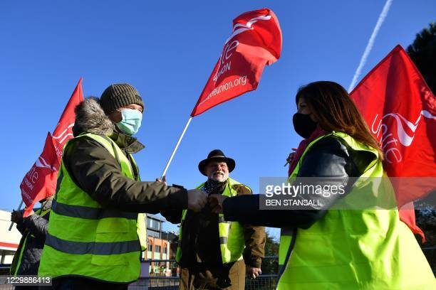 Demonstrators wearing face masks or coverings due to the COVID-19 pandemic, touch fists as they stand on a picket line near London's Heathrow Airport...