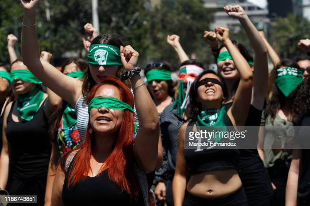 """Demonstrators wearing green handkerchiefs covering their eyes sing and dance in a feminist flash mob performing """"Rapist in Your Path"""" in protest of..."""