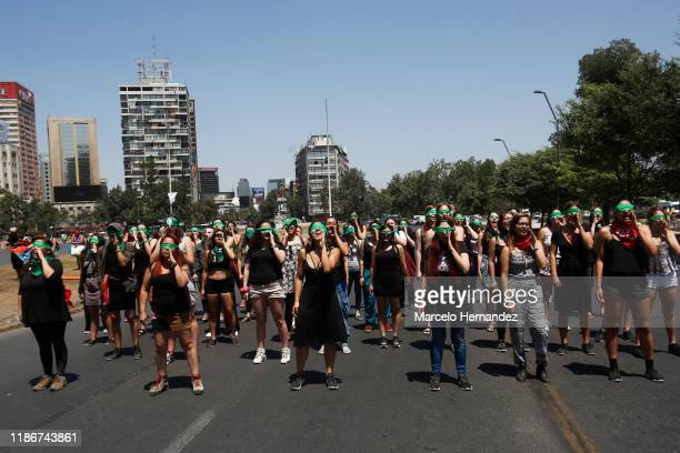 "Demonstrators wearing green handkerchiefs covering their eyes sing and dance in a feminist flash mob performing ""Rapist in Your Path"" in protest of..."