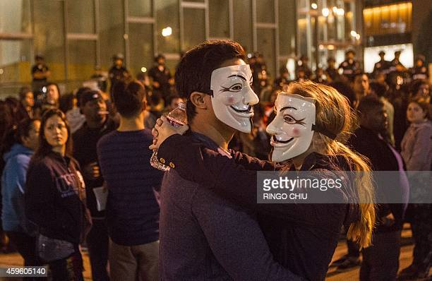 Demonstrators wearing Guy Fawkes mask are seen in front of Los Angeles police headquarters on November 25, 2014 in Los Angeles during demonstrations...