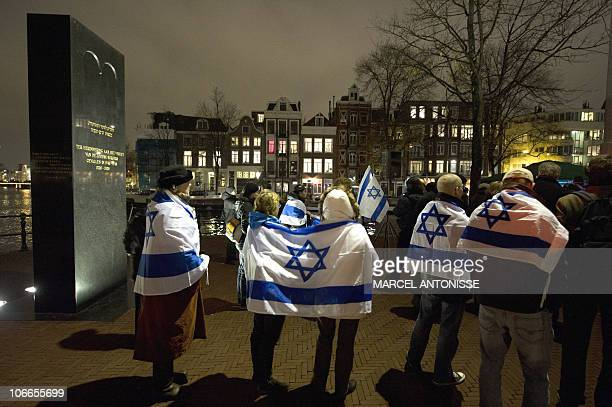 Demonstrators wearing Israeli flags march in Amsterdam on November 9 2010 in remembrance of the Kristallnacht or the Night of Broken Glass pogrom...