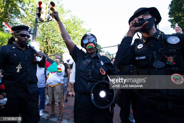 Demonstrators wearing logos of the New Black Panther Party speak during a protest at Lafayette Square near the White House, against police brutality...