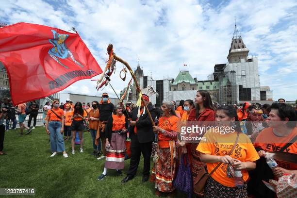 Demonstrators wearing orange in solidarity with survivors of residential schools gather in front of Parliament Hill on Canada Day in Ottawa, Ontario,...