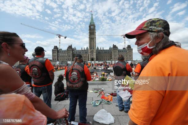 Demonstrators wearing orange in solidarity with survivors of residential schools gather at a memorial in front of Parliament Hill on Canada Day in...