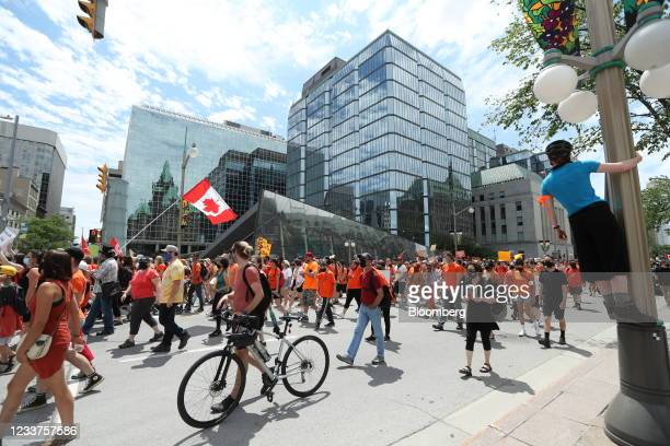 Demonstrators wearing orange in solidarity with survivors of residential schools march past the Bank of Canada to Parliament Hill on Canada Day in...
