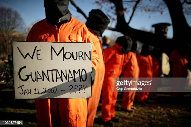Demonstrators wearing orange jumpsuits and hoods over their heads rally to demand closure of the detention camp at the U.S. Naval Station in...