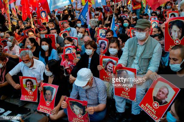 Demonstrators, wearing protective face masks, display portraits of victims during a protest to mark the anniversary of the 2015 suicide attack in the...