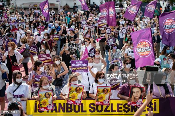 Demonstrators, wearing protective face masks, hold placards and portraits of women, during a protest called by KCDP and Womens Assemblies, for a...