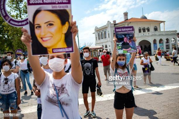 Demonstrators wearing protective face masks, hold portraits of women and placards reading 'we are not quiet', during a protest called by KCDP and...