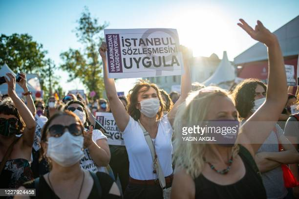 Demonstrators wearing protective face masks hold up placards during a demonstration for a better implementation of the Istanbul Convention and the...