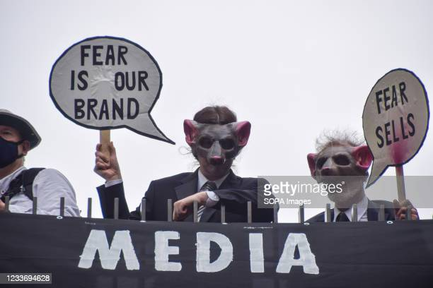 Demonstrators wearing rat masks hold placards during the Free The Press protest. Extinction Rebellion demonstrators marched from Parliament Square to...