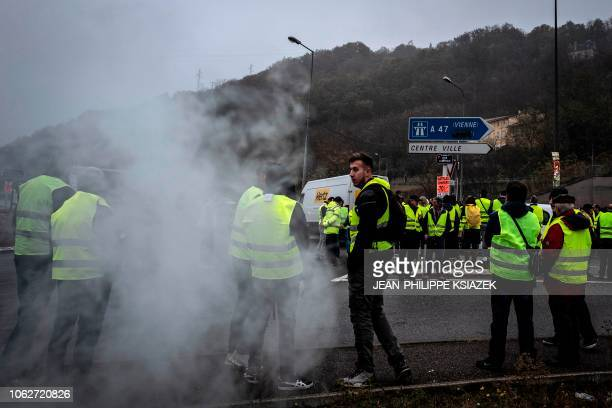 Demonstrators wearing yellow vests stand amid smoke during a protest against the rising of the fuel and oil prices on November 17 2018 in front...