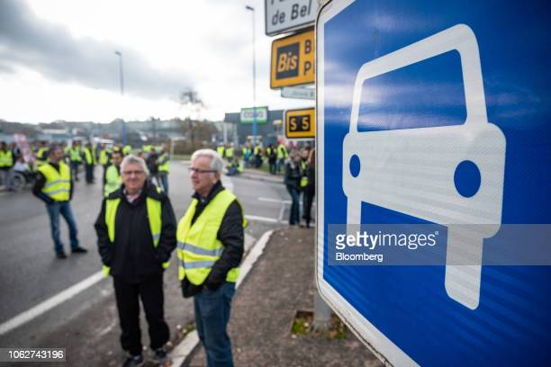 Demonstrators wearing yellow vests stand next to a road sign as they block the highway to Rodez during a protest against fuel costs near Rodez,...