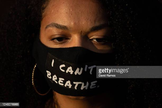 Demonstrators wears a protective face mask where it reads 'I can't Breathe' while gathering to mourn the death of George Floyd during a vigil at...