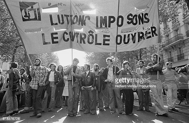 """Demonstrators with a banner reading, """"Let us Fight and Impose Workers' Control,"""" take to the streets of Paris to protest against Prime Minister..."""