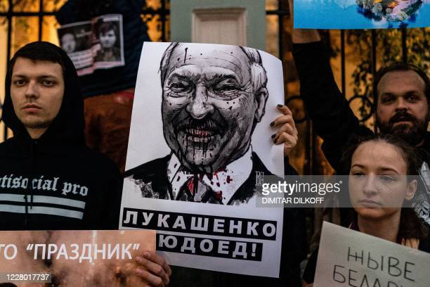 TOPSHOT Demonstrators with a placard with an image of Belarus' President Alexander Lukashenko protest against the results of Belarusian presidential...