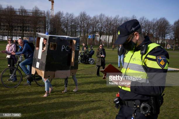 Demonstrators with a police car made of cardboard walk past a policeman at the demonstration held on February 20, 2021 in The Hague, Netherlands....