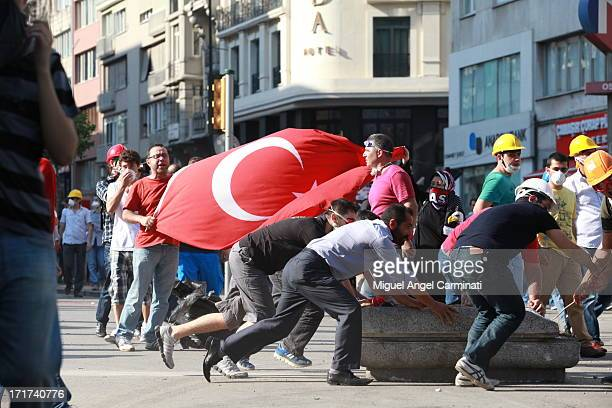 Demonstrators with a Turkish flag and others building a barricade in Osmanbey area near Taksim Square during the riots at Istanbul.