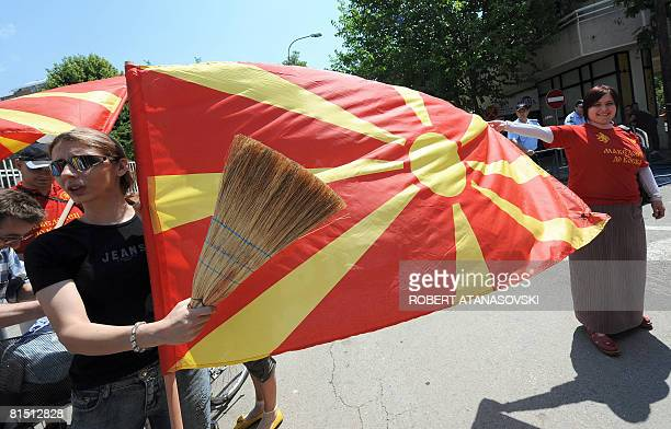Demonstrators with brooms hold the flag as others clean up the pavement in front of the Greek diplomatic office in Skopje Republic of Macedonia in a...