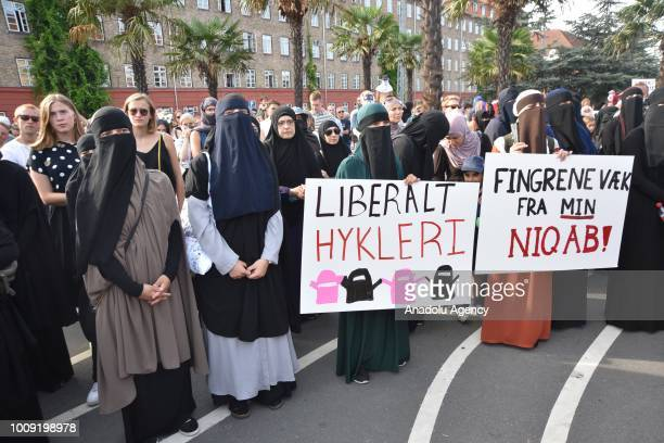 Demonstrators with face veils hold placards and banners as they gather to protest ban on the wearing of face veils at the Black Square in Copenhagen...