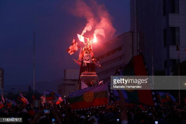 Demonstrators with flares and the picture of Camilo Catrillanca climb the monument at Plaza Italia during a protest against president Sebastian...